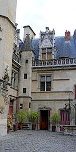 Photo prise à l'intérieur de la cour de l'Hôtel de Cluny : les pavés, la porte, une tourelle, une belle fenêtre au 2ème étage, ...